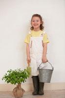 バケツを持つ長靴を履いた女の子と苗木 21086000633| 写真素材・ストックフォト・画像・イラスト素材|アマナイメージズ