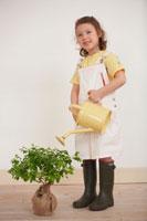 黄色いじょうろで苗木に水をやる女の子 21086000642B| 写真素材・ストックフォト・画像・イラスト素材|アマナイメージズ