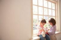 窓辺で遊ぶハーフの姉妹