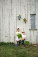 苗木を持って庭に立つハーフの姉妹
