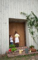 木の戸を覗くハーフの姉妹