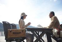 テラス席でお茶を飲むカップルと旅行かばんと湖