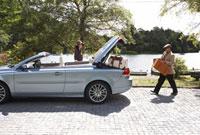 車に旅行かばんを積むシニア夫婦