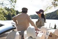 湖を見るシニア夫婦と車