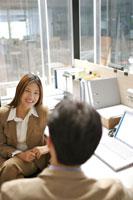 オフィスで向き合って話すビジネスマンとOL 21087000034A| 写真素材・ストックフォト・画像・イラスト素材|アマナイメージズ