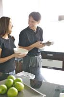 キッチンで皿を運ぶカップル