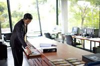 引き出しの中を見るビジネスマン 21087000102A| 写真素材・ストックフォト・画像・イラスト素材|アマナイメージズ