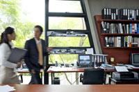 オフィスの中を歩くビジネスマンとOL 21087000104D| 写真素材・ストックフォト・画像・イラスト素材|アマナイメージズ