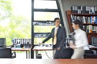 オフィスの中を歩くビジネスマンとOL