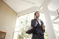 新聞とりんごを持ち歩きながら電話をするOL 21087000234D| 写真素材・ストックフォト・画像・イラスト素材|アマナイメージズ