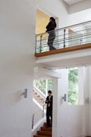 渡り廊下を歩くOLと階段を降りるビジネスマン 21087000235C| 写真素材・ストックフォト・画像・イラスト素材|アマナイメージズ
