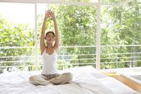 ベッドの上でストレッチをする女性 21087000239B| 写真素材・ストックフォト・画像・イラスト素材|アマナイメージズ
