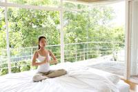 ベッドの上でストレッチをする女性 21087000241| 写真素材・ストックフォト・画像・イラスト素材|アマナイメージズ