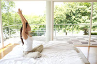 ベッドの上でストレッチをする女性 21087000245B| 写真素材・ストックフォト・画像・イラスト素材|アマナイメージズ