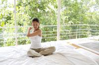 ベッドの上でストレッチをする女性 21087000246| 写真素材・ストックフォト・画像・イラスト素材|アマナイメージズ