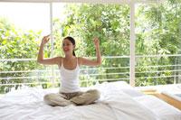 ベッドの上でストレッチをする女性 21087000247| 写真素材・ストックフォト・画像・イラスト素材|アマナイメージズ