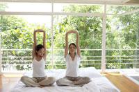 ベッドの上でストレッチをする2人の女性 21087000251A| 写真素材・ストックフォト・画像・イラスト素材|アマナイメージズ