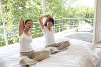 ベッドの上でストレッチをする2人の女性 21087000252C| 写真素材・ストックフォト・画像・イラスト素材|アマナイメージズ