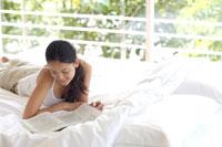 ベッドの上で本を読む女性