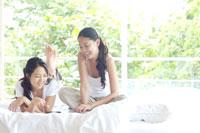 ベッドの上で本を読む2人の女性