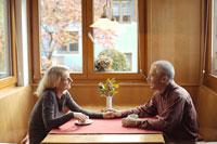 手を握り向かい合いお茶を飲む夫婦