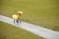 傘をさして犬の散歩をする母と子