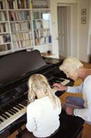 孫にピアノを教える祖母 21087000486| 写真素材・ストックフォト・画像・イラスト素材|アマナイメージズ
