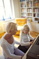 孫にピアノを教える祖母