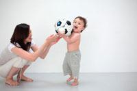 サッカーボールで遊ぶ母と子