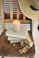 イスの上の本と麦藁帽とキャンドルとオレガノのドライフラワー
