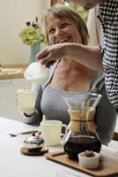 女性のカップにミルクを入れる男性