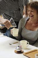 女性のカップにコーヒーを入れる男性
