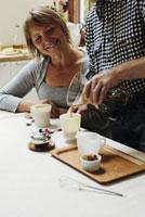 女性とカップにコーヒーを入れる男性