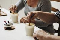 シナモンスティックでコーヒーをまぜる老夫婦 21090001177  写真素材・ストックフォト・画像・イラスト素材 アマナイメージズ