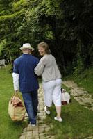 旅行バッグを持って歩く老夫婦の後姿