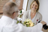 女性のグラスにワインを注ぐ男性