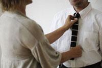 男性のネクタイを直す女性 21090001209  写真素材・ストックフォト・画像・イラスト素材 アマナイメージズ