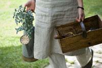 ジョウロと木箱を持つ女性の手元