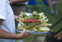 焼けた野菜を持つ男性の手元