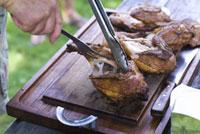 焼けた鶏肉を切る男性の手元
