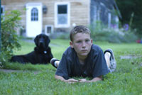 芝生の上にうつぶせになる子供と犬