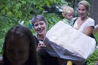 荷物を運ぶ女性と子供を抱っこする女性