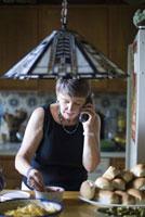 キッチンで電話をする女性