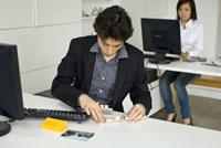机で模型を組み立てる男性