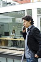 ベランダにいる男性とオフィスの中の女性
