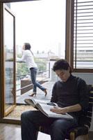 ベランダの女性とイスに座って本を読む男性