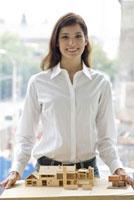 家の模型を持つ女性 21090001635A| 写真素材・ストックフォト・画像・イラスト素材|アマナイメージズ