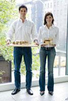 家の模型を持つ男女