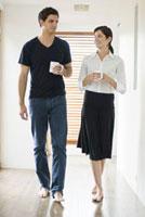 マグカップを持って歩く男女