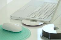 白いデスクの上のパソコンとマウスとディスク